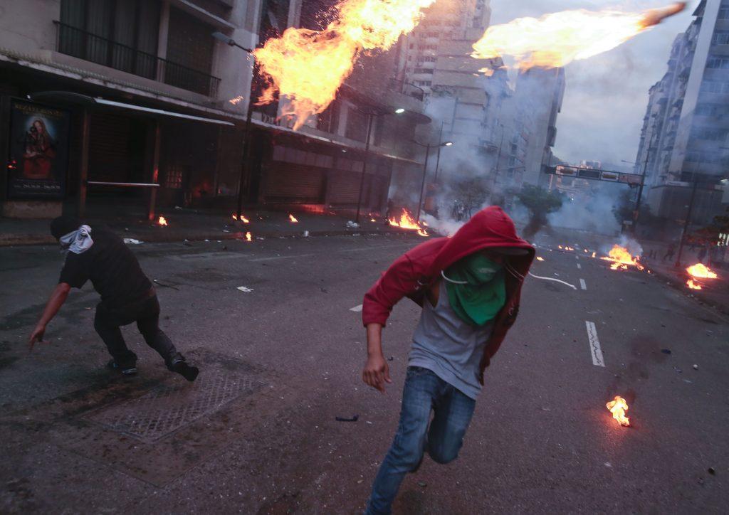 Manifestantes corren tras lanzar bombas molotov durante enfrentamiento con la policía bolivariana en una protesta antigubernamental en Caracas, Venezuela, el sábado 15 de marzo de 2014.(AP Photo/Esteban Felix)